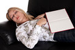Beautiful blond girl fell asleep with her book on the couch
