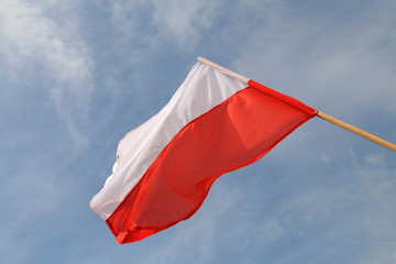 Polish flag waving in the wind on the cloudy sky