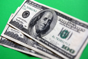 three 100 dollars banknote on the green background