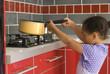 Jeune fille tenant une casserole sur la cuisinière