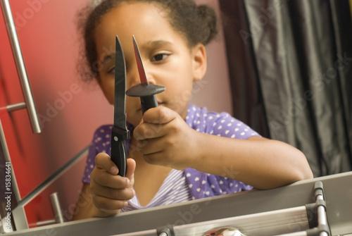 Danger accident domestique - jeune fille touchant aux couteaux