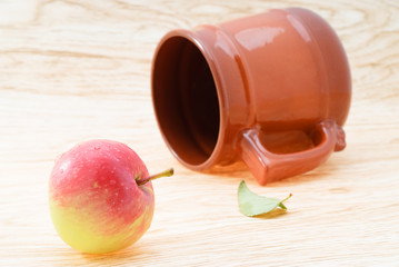 Clay mug and ripe red apple