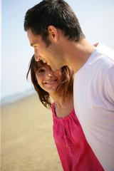 homme et femme souriants se promenant en bord de plage