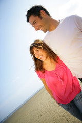 homme et femme souriants se baladant à la plage