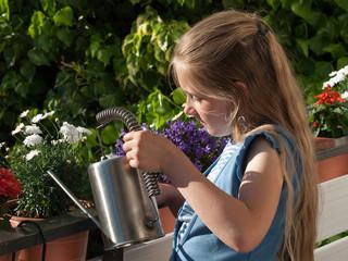 Kind gießt Balkonblumen