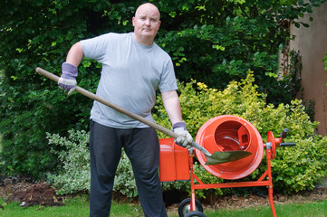 male outside in garden with sand cement mixer