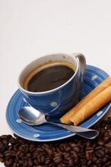 blaue tasse kaffee mit knusperröllchen