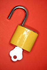 Open padlock and key on red