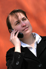 Business women is phoning at orange wall