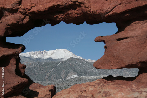 Pikes Peak mountain as seen through a hole in red rocks at Garde