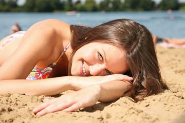 frau am strand liegt im sand und lächelt