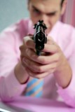 Businessman point his handgun to camera