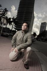Man squatting on a street corner