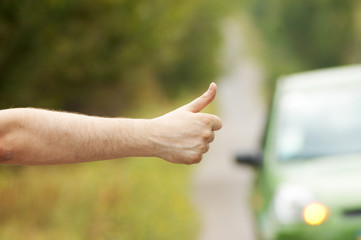 Man hand hitching car on road