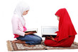 A young muslim girls in traditional clothes reading Koran