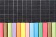 Craies de couleur alignées sur ardoise quadrillée