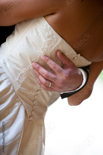 Close up of the groom's hand embracing the bride.