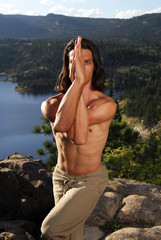 Man doing yoga on a mountain top