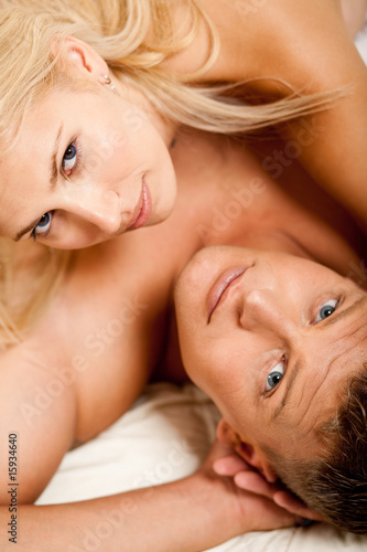portrait of semi nude couple laying in bed