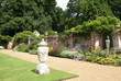 garden path view. decorative garden wall with statue. vase