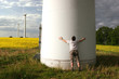 Man embraces a Windmill in front of a rape field