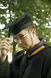 Funny graduate liiks on his cap's tassel