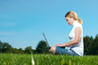 The girl with laptop on a green lawn