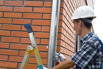 Man installing  rain gutter system
