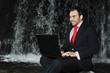 man with laptop in front of the waterfall