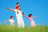 Happy family with four members on beautiful scene in nature poster