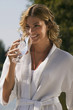 Frau im Bademantel, mit Glas Wasser