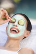 Junge Frau mit Gesichtsmaske und Gurkenscheiben