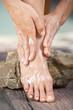 Frau cremt Füße ein