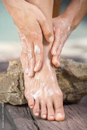 Woman applying lotion to feet, low section