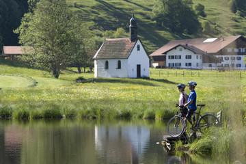 Deutschland, Bayern, Allgäu, Paar mit Mountainbikes am Seeufer