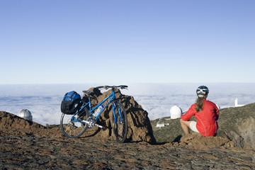 Spanien, Kanarische Inseln, La Palma, Frau mit Mountainbike bei einer Pause