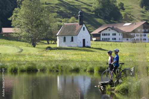 Germany, Bavaria, Allgaeu, Couple with mountain bikes standing on lakeshore