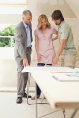 Junges Paar und Architekt auf der Baustelle
