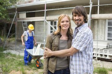 Junges Paar umarmen auf der Baustelle, Bauarbeiter