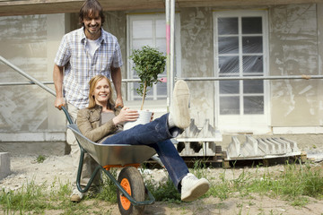 Junges Paar auf der Baustelle, Mann fahren Frau in Schubkarren