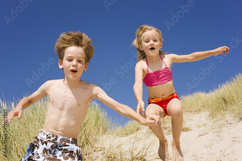Germany, Baltic sea, Boy (8-9) and girl (6-7) jumping down beach dune