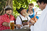 Germany, Bavaria, Upper Bavaria, People in beer garden playing cards