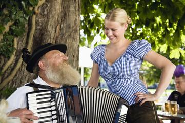 Deutschland, Bayern, Senior Mann in traditioneller Tracht spielen Akkordeon in Biergarten