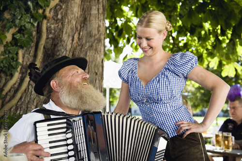 Germany, Bavaria, Upper Bavaria, Senior man in traditional costume playing accordion in beer garden