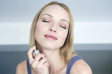 Frau jung sprühen auftragen Parfüm auf Hals, Portrait
