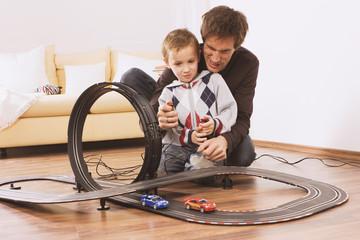 Vater und Sohn spielen mit Spielzeugauto Rennauto