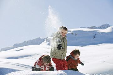 Italien, Südtirol, Seiseralm, Kinder werfen Schnee in der Luft