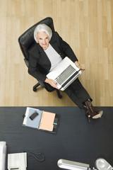 Deutschland, München, Senior Geschäftsfrau im Büro, mit Laptop,