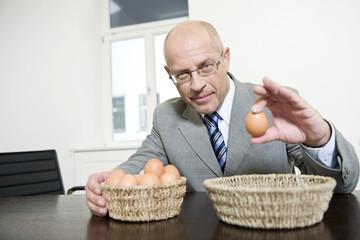 Deutschland, München, Geschäftsmann halten Ei, Portrait
