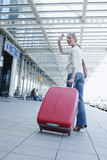 Germany, Leipzig-Halle, Airport, Young woman with suitcase, waving